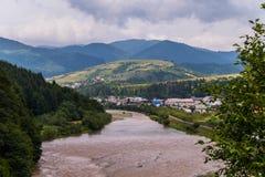 山山河的风景、全景,村庄、绿色草甸和倾斜反对多云天空背景 库存图片