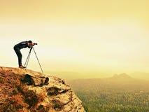 山山顶工作的野生生物摄影师 人喜欢旅行和摄影,拍照片 图库摄影