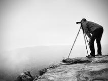 山山顶工作的野生生物摄影师 人喜欢旅行和摄影,拍照片 库存照片