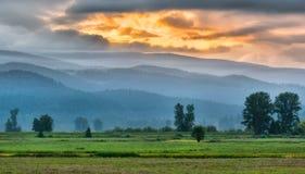 山山麓小丘与橙色日出的 库存照片