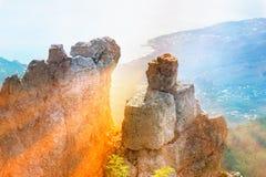 山岩石和石头与太阳和鸟瞰图海边光芒的  免版税库存照片