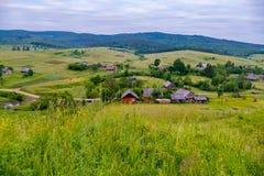 山岭地区一个迷人的风景有位于倾斜和谷的农村房子的在绿色树之间 免版税库存照片