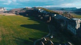 山峭壁和几个小屋的顶视图一个绿色领域的反对蓝色多云天空 美好的夏天 股票视频