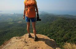 山峰峭壁的妇女摄影师 图库摄影