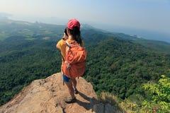 山峰峭壁的妇女摄影师 库存照片