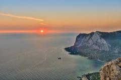从山峰的惊人的看法在岩石、五颜六色的天空和海在晚上 在日落的山横向 自然 免版税图库摄影