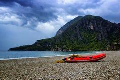 山惊人的风景与红色小船的在有石海滩和蓝天的海附近 Olympos海滩,土耳其 免版税图库摄影