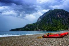 山惊人的风景与红色小船的在有石海滩和蓝天的海附近 Olympos海滩,土耳其 免版税库存图片