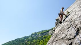 山指南一条平板石灰石上升的路线的攀岩运动员在瑞士的阿尔卑斯在一美好的天 免版税库存照片