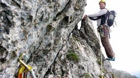 山指南在一个陡峭的上升的路线标题边缘的攀岩运动员到下沥青里 免版税库存照片