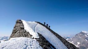 山指南在有两个客户的瑞士阿尔卑斯到达山顶 免版税库存照片