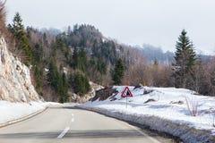 山有一个警报信号的冬天路 免版税库存照片