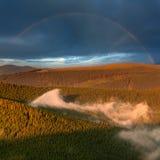 山有薄雾的森林和彩虹在雨以后 免版税库存图片