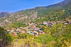 山村Pedoulas,塞浦路斯。在房子、山和圣洁十字架大教会屋顶的看法。村庄是一个多数pictu 免版税库存图片