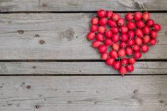 山楂树莓果的红色心脏在木背景的 库存图片