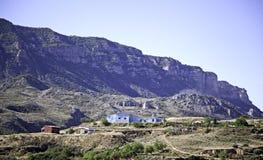 山横向有蓝色房子背景 免版税图库摄影