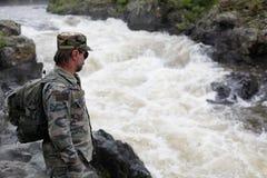 山河的岸的远足者。 免版税库存照片
