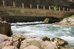 山河跑在山,岩石的一座老桥梁下 免版税库存图片