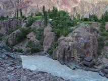 山河:一条蓝蓝灰色小河流经伯根地峭壁,绿色灌木一道狭窄的峡谷,并且树在镇压增长  图库摄影