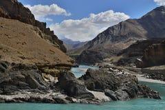 山河:漏在与冰砾,与云彩的蓝天的棕色岩石之间的绿松石颜色镇静流程 库存照片