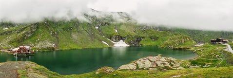 山湖的全景 山Balea湖的典型的高山房子 图库摄影