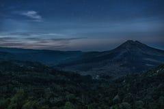 山火山Batur的剪影在背景夜空的与星 免版税库存图片