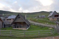 山牧羊人村庄小屋的风景图象有森林和蓝天看法在背景中 免版税库存照片