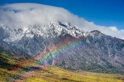 山环境美化与在淡色的彩虹多云天空您的设计的 浪漫海景-海边视图与 库存照片