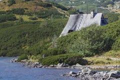 山瑞士山中的牧人小屋 木旅舍屋顶在矮小的杉木tr之间的 免版税库存照片
