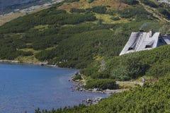 山瑞士山中的牧人小屋 木旅舍屋顶在矮小的杉木tr之间的 免版税库存图片