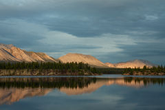 山由日落光和他们的反射点燃了在湖 免版税库存图片