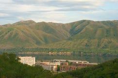 山的一个小镇在河岸 免版税库存照片