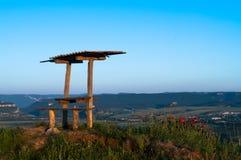 以山的上面为背景有桌,并且旅客游人的长凳点燃了金黄火热的轻的aroun 库存图片