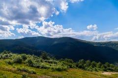 山的上面在一朵大云彩附近的与灌木和树丛林  免版税图库摄影