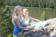 山的两个女孩读了地图近 库存照片