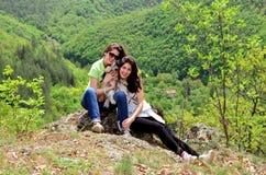 山的两个微笑的姐妹与他们的狗 库存图片