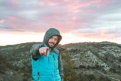 山的人指向照相机的 做一个正面姿态的登山家 库存图片
