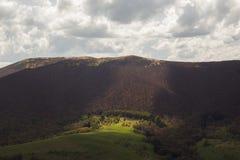 山的全景长满与绿草和棕色树与发光通过云彩的太阳 库存照片