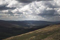 山的全景长满与黄色草和黑暗的树与发光通过云彩的太阳 库存图片