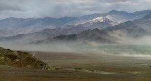 山的剪影在尘暴期间的,沙子墙壁创造阴霾和旅行沿地面,一场难以置信的风暴,喜马拉雅山, 库存图片