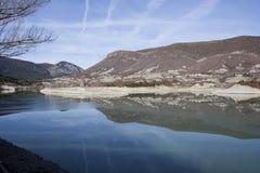 山的反射在阿尔吉斯水库的  库存照片