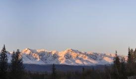 山的多雪的山峰的一个精神看法用朝阳的光芒填装了 免版税库存照片