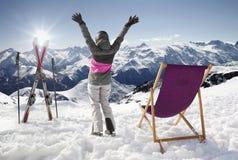 山的妇女在与太阳懒人的冬天,法国高山 免版税库存图片