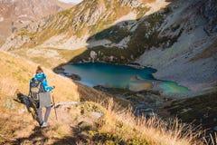 山的妇女背景的远足者和湖 旅游妇女下降山 库存照片