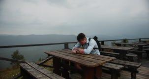 山的孤独的人 年轻英俊的人说谎他的在坐在桌上的胳膊的头有巨大看法 股票视频