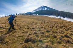 山的孤独的摄影师与在一个三脚架的一台照相机在co 库存照片