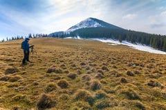 山的孤独的摄影师与在一个三脚架的一台照相机在co 免版税库存图片