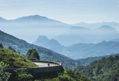 山的孤独的骑自行车者 免版税库存图片
