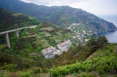 山的意大利村庄与海岸线和桥梁 免版税图库摄影