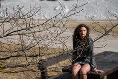 山的深色的波浪发女孩,性感坐一张巨型的木桌 免版税库存照片